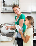 Girl helping mother washing dishes Stock Images