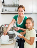 Girl helping mother washing dishes Stock Photography