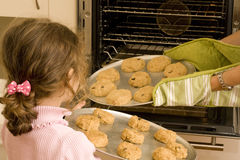 Girl helping mum bake cookies in oven. Girl helping mum bake cookies standing in front of oven with trays Royalty Free Stock Photos