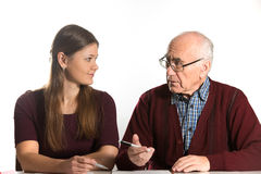 Girl helping senior. Young women helping senior men to fill paper documents Stock Photo
