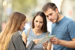 Girl helping to a couple of tourists to find a location. In a paper map on the street stock photography