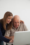 Girl helping to her grandfather with the computer Royalty Free Stock Images