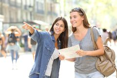 Girl helping to a tourist who asks direction. Happy girl helping to a tourist who asks direction in the street stock photos