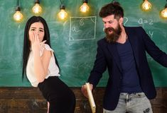 Girl on helpless face punished by teacher. Schoolmaster punishes student with slapping on her buttocks with book. Man with beard slapping student, chalkboard stock photos