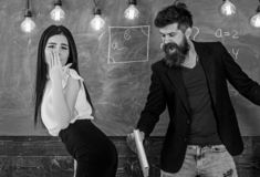 Girl on helpless face punished by teacher. Schoolmaster punishes student with slapping on her buttocks with book. Man with beard slapping student, chalkboard royalty free stock photos