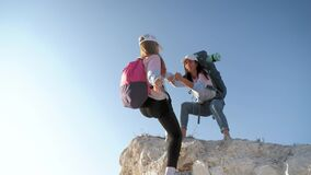 Girl helps her friend climb up the last section of mountain. Tourists with backpacks help each other, silhouette with
