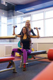 Girl helps her friend to workout with dumbbells Royalty Free Stock Photos
