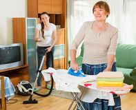 Girl helps her mature mother with cleaning Royalty Free Stock Photography
