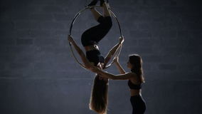 The girl helps her partner to do the trick on the aerial hoop stock video footage