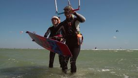 UKRAINE, GENICHESK - AUGUST 11, 2018: A A smiling woman in a suit for diving gives a man a board for kitesurfing, slow. The girl helps a man on kitesurfing, the stock video footage