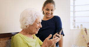 Girl Helps Old Woman Using Mobile Phone And Technology Royalty Free Stock Photo