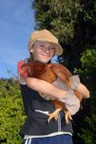 Girl with hen. Little girl with hat holding a red hen stock image