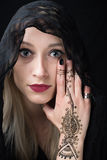 Girl with henna on her hand covering one eye Stock Photo