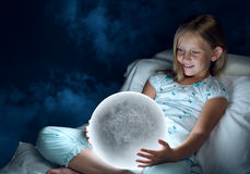Girl in her bed and moon planet Stock Photography