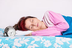 Girl in her bed sleeping next to the alarm clock Stock Image