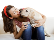 Girl with her best friend. Beautiful girl receiving a kiss from her best friend, a nice and cute dog Royalty Free Stock Images