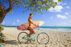 Girl on her bicycle with surfboard stock photo
