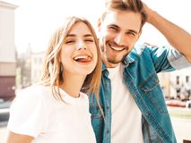 Girl and her boyfriend posing in the street. Portrait of smiling beautiful girl and her handsome boyfriend. Woman in casual summer jeans clothes. Happy cheerful royalty free stock photography