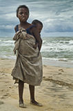 The girl and her brother. Image of a poor girl carrying her brother at the beach of Manakara (Madagascar). Madagascar is a developing country where poverty is Royalty Free Stock Photo