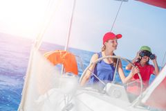 Girl with her brother on board of sailing yacht on summer cruise. royalty free stock images