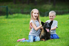 Girl and her brother. Playing with dogs on grass Royalty Free Stock Images
