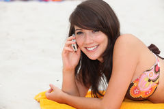 Girl on her cellphone. On the beach Stock Image