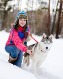 Girl with her cute dog in the winter forest Stock Image