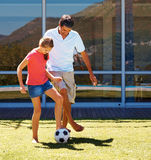 Girl and her dad playing football Royalty Free Stock Photo