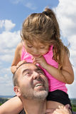 Girl on her dads shoulders. Father takes his daughter on his shoulders for a walk stock image