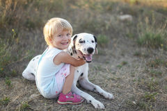 A girl and her dog. A cute little girl and her dog outdoor during summer Stock Photos