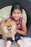 Girl and her dog. Young girl sitting with her pomeranian dog sitting in a tire stock images