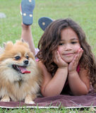 Girl and her dog. Girl poses for a picture with her pet pomeranian dog Royalty Free Stock Photo
