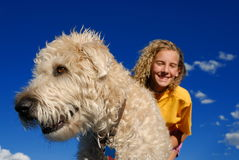 Girl and her dog. With blue sky. Closeup on dog. Girl wearing yellow shirt stock image