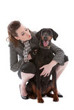 Girl and her dog. Young fashionable brunette with her doberman pincher on white background Royalty Free Stock Photography