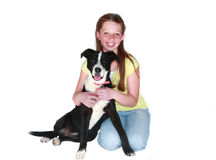 Girl and her dog. Cute young tween girl sitting with her black and white dog against a white background Stock Images