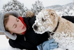 Girl with her dog. Girl with her wheaten terrier playing in snow Royalty Free Stock Images