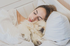 Girl and her dog in the bed. Beautiful girl and her dog in the bed stock photo