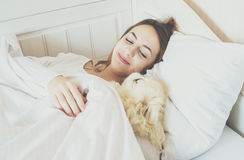 Girl and her dog in the bed. Beautiful girl and her dog in the bed royalty free stock image