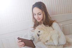 Girl with her dog on the bed with tablet. Royalty Free Stock Photo