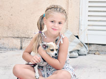 Girl with her dog. Little girl holding dog on her knees Royalty Free Stock Image