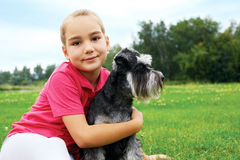 Girl and her dog lying on the grass in the park on a summer day Stock Image