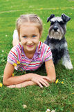 Girl and her dog lying on the grass in the park on a summer day Royalty Free Stock Photos