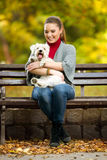 Girl and her dog maltezer in a park Stock Images