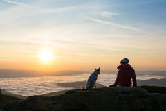 Girl and her dog relaxing on a peak stock image