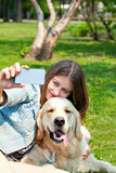 Girl and her dog selfie summer on a background of green grass Royalty Free Stock Photos
