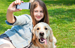 Girl and her dog selfie summer on a background of green grass. Royalty Free Stock Photography