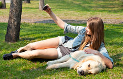 Girl and her dog selfie summer on a background of green grass.. Royalty Free Stock Images