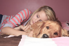 Girl and her dog sleeping together on a bedroom stock photos