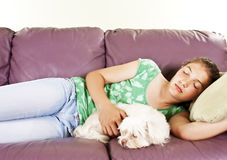 Girl and her dog sleeping together on a sofa Royalty Free Stock Images