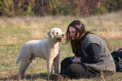 Girl and her dog. Girl speaks something to her dog Royalty Free Stock Image